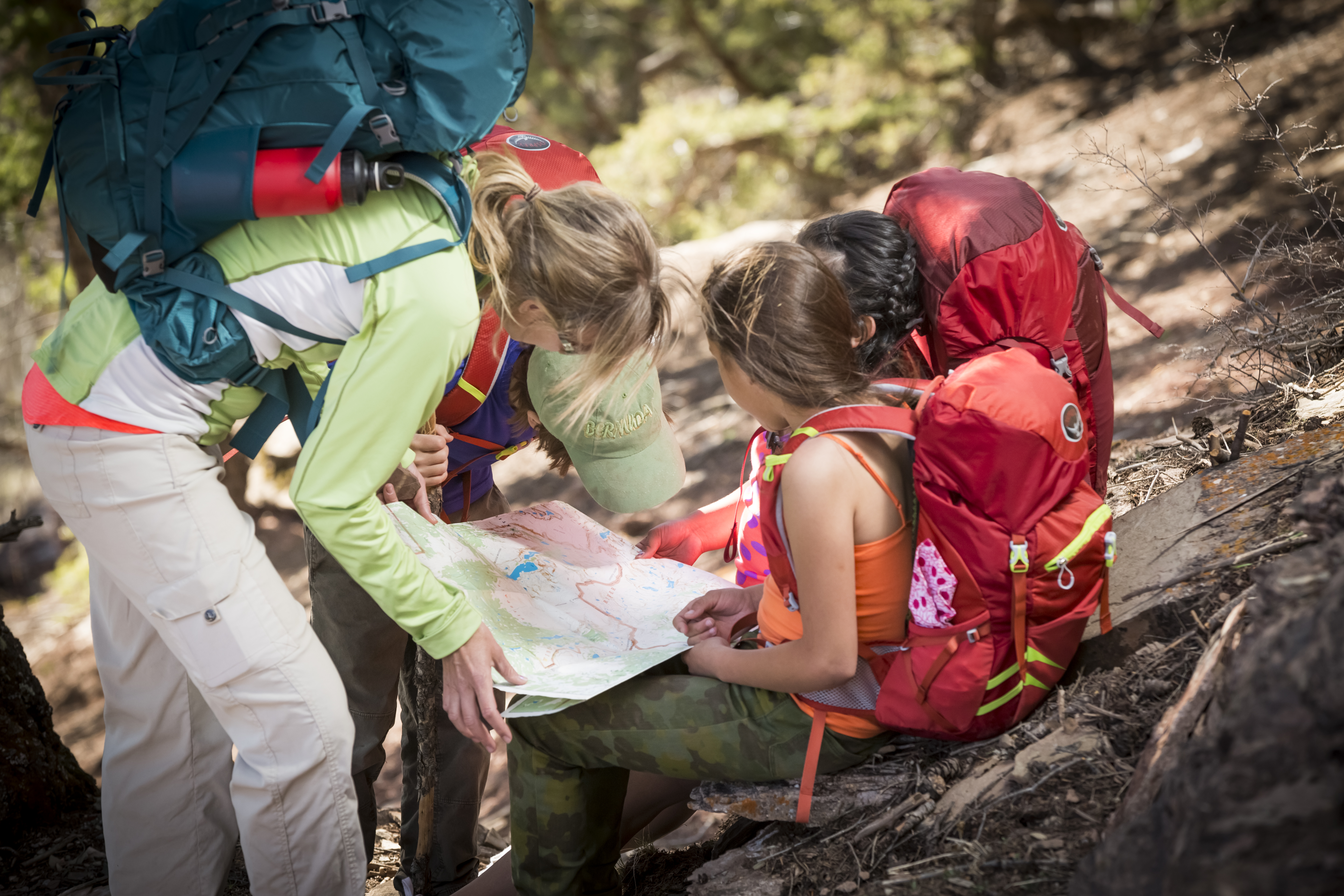 a family hiking looking at a map - representing Tips for Buying a Backpack