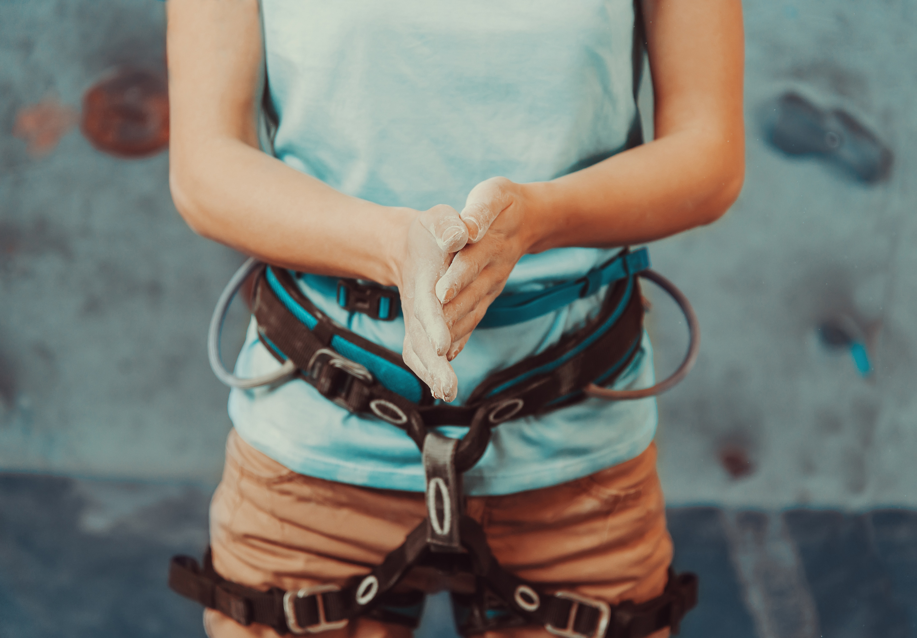Climbing Guide For Beginners - women clapping her hands together in a climbing harness on the ground