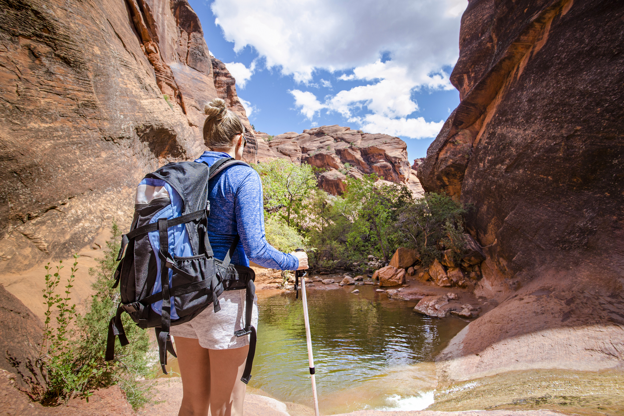 backpacking - Rear view of a Woman hiking to a waterfall in a red rock canyon. She is experiencing desert beauty in the United States. Looking down at this natural water slide in a slot canyon
