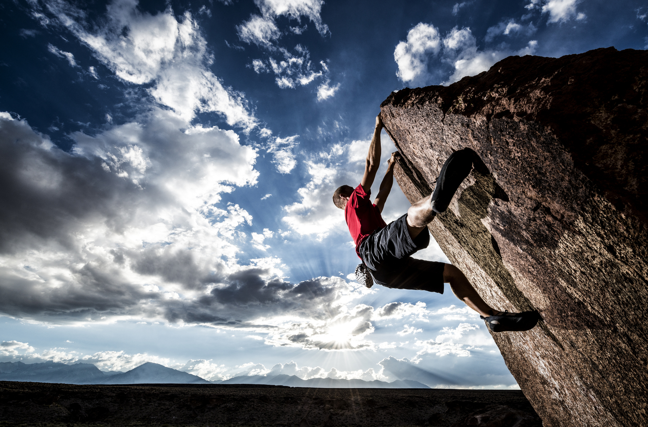 Rock climber bouldering on the side of a cliff in a dramatic setting