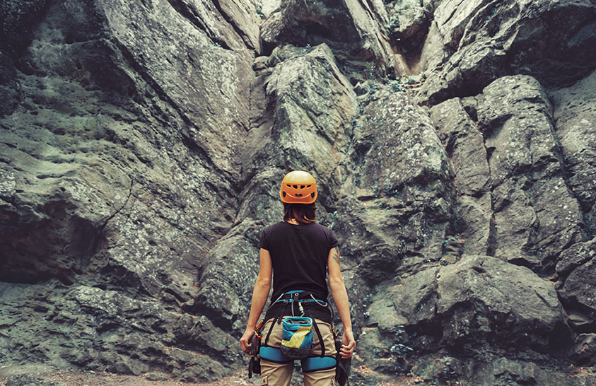 Young woman wearing in climbing equipment standing in front of a stone rock outdoor and preparing to climb, rear view representing rock climber gift ideas