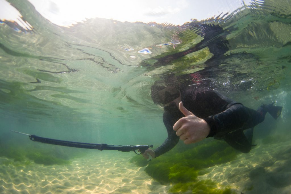 A real scene of a young man giving a 'thumps up' while spear fishing of the Cornwall coast. The photograph shows the spear fisherman in shallow water, you can see the sand of the sea bed and the top of the ocean. Sunlight can also be seen shining through the water and onto the sea bed. spearfishing a concept