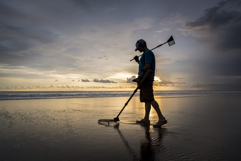 During sunset and at low tide, a Caucasian adult walks along the beach and by using a metal detector he is trying to find some hidden treasures. He is using a sophisticated device from the military and hopes to find possible gold and jewelry covered under the sand.