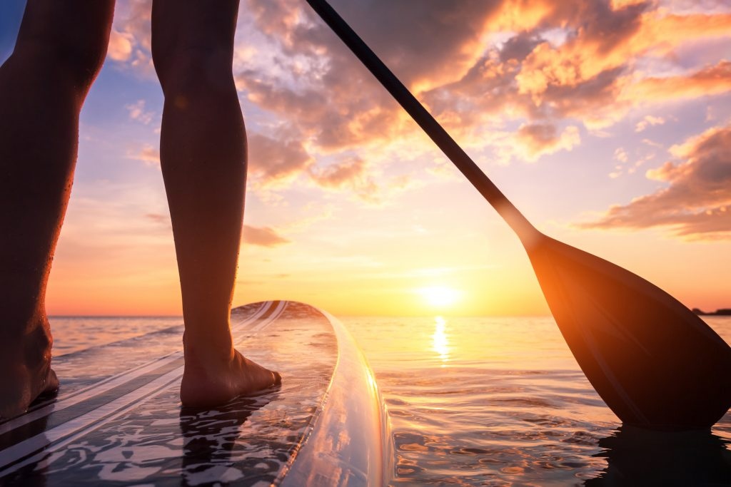 Stand up paddleboarding or standup paddleboarding on quiet sea at sunset with beautiful colors during warm summer beach vacation holiday, active woman, close-up of water surface, legs and board representing paddleboarding